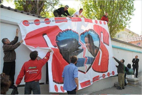 Общественники вывешивают баннер, призывающий спасти севастопольский дельфинарий в Арт-бухте